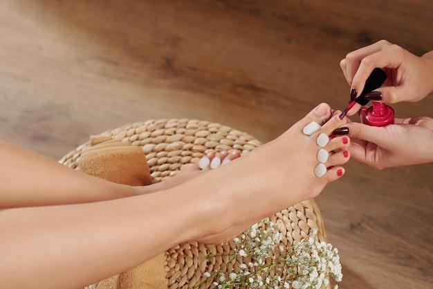 Estetista che applica smalto per unghie