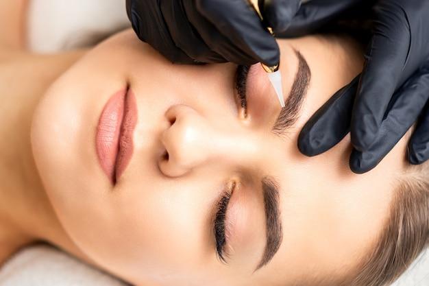 Estetista che applica trucco permanente sulle sopracciglia di giovane donna con una speciale macchina utensile per tatuaggi