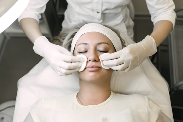 L'estetista pulisce la pelle del paziente con un batuffolo di cotone