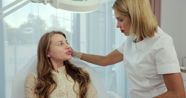 L'estetista consulta la donna sull'iniezione di botox facciale nel primo piano del salone di bellezza.
