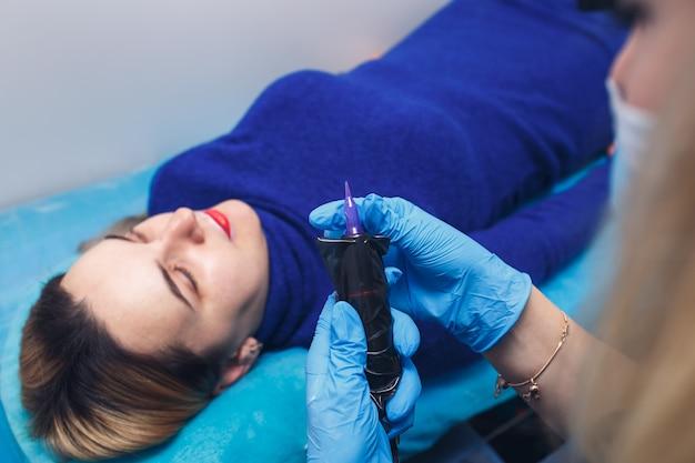 Estetista cosmetologo prepara macchinetta per tatuaggi per il trucco permanente delle labbra