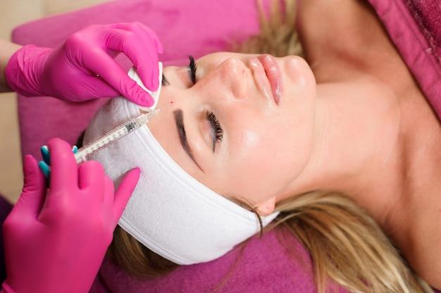 Mani di medico dell'estetista che fanno procedura di bellezza al fronte femminile con la siringa. medicina estetica e chirurgia, concetto di iniezioni di bellezza
