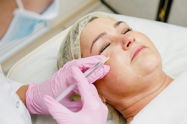 Estetista che fa iniezione facciale. procedura cosmetologica rivitalizzante antietà