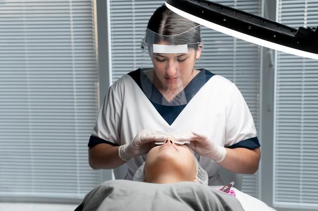 Estetista che esegue una procedura di microblading su una donna