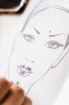 Estetista che disegna la zona dell'attività mimica nella cartella del paziente nell'ufficio di cosmetologia