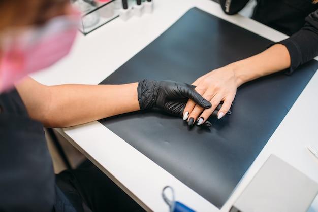 L'estetista in guanti pulisce la vecchia vernice dalle unghie