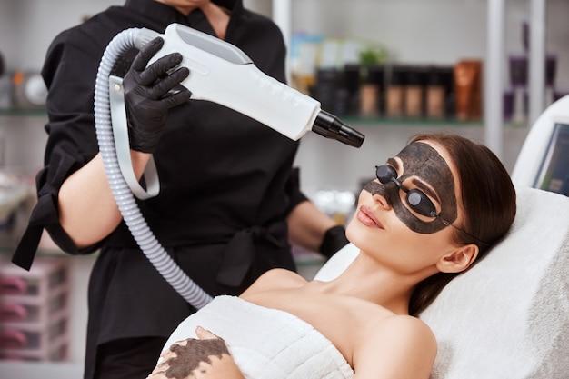 Estetista che tiene il laser di bellezza vicino al viso di donna coperto con maschera di carbonio e occhiali protettivi, procedure termali con laser e maschere nere