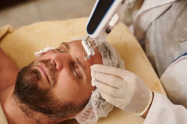 Estetista che tiene la pistola di mesoterapia e uomo barbuto al salone di bellezza che riceve il trattamento della pelle di ringiovanimento