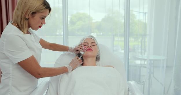 L'estetista inietta acido ialuronico nelle labbra di una ragazza con una siringa. il medico cosmetologo esegue la procedura nell'ufficio di cosmetologia.