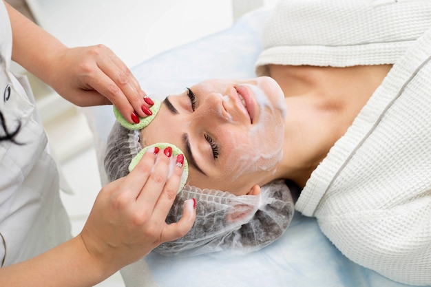 L'estetista fa la pulizia e l'esfoliazione del viso per una bella ragazza. salone di bellezza.