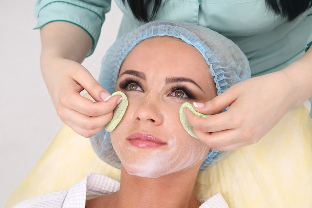 L'estetista fa la pulizia e l'esfoliazione del viso per una bella ragazza