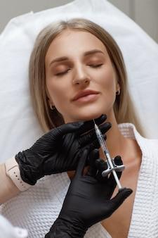 Estetista che fa iniezione in volto di donna, primo piano. procedura di biorivitalizzazione. chirurgia plastica. salone di cosmetologia