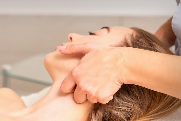 Estetista che fa massaggio linfodrenante al viso o massaggio lifting al salone di bellezza.