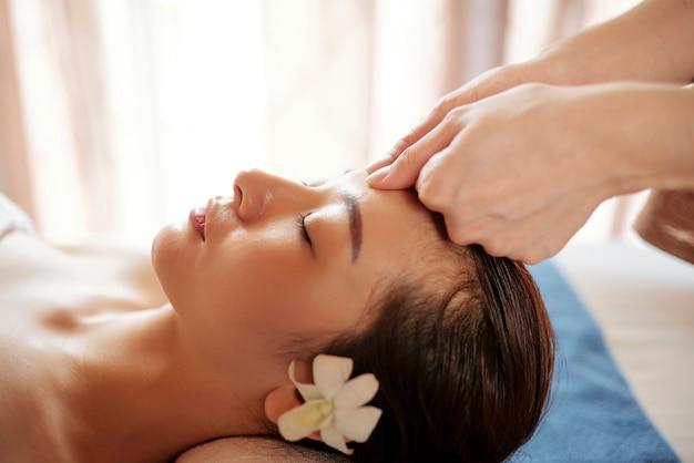 Estetista che massaggia fronte del cliente