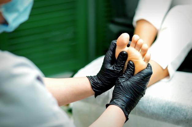 Estetista in guanti di gomma protettivi che fa massaggio sulla pianta del piede femminile in un salone di bellezza spa