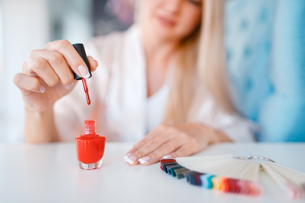 Salone di estetista, manicure, donna con smalto rosso.