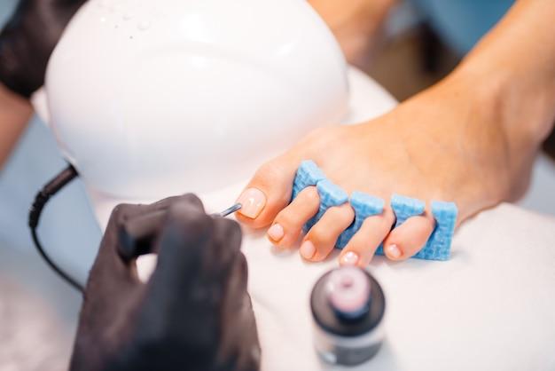 Salone di estetista, pedicure, primo piano della procedura di applicazione della vernice.