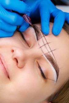 Estetista che tatua le sopracciglia di una donna utilizzando attrezzature speciali durante il trucco permanente, primo piano.