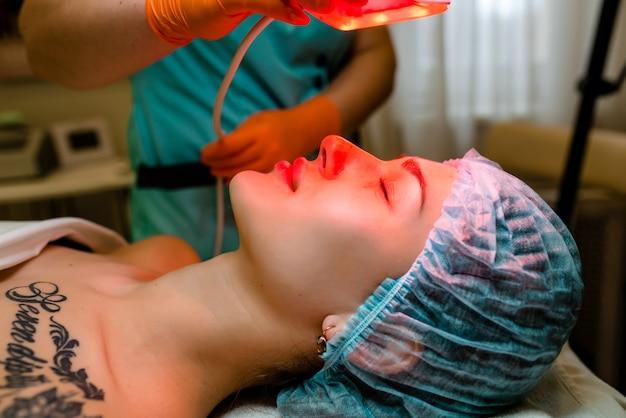 Estetista utilizzando raggi viola sul volto di una giovane donna