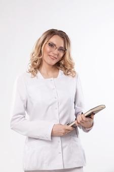 L'estetista in una veste bianca è in studio su una parete bianca