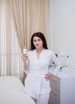 L'estetista in uniforme bianca sta in piedi e tiene in mano un dispositivo per la pulizia del viso ad ultrasuoni in ufficio