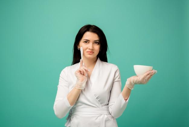Estetista in uniforme bianca sta con una spatola e una tazza sul blu
