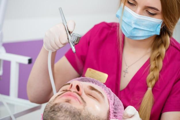 Estetista donna che fa la procedura di pulizia del viso ad ultrasuoni per il giovane in clinica. ritratto del cliente della mano e del primo piano, vista laterale del primo piano. procedura nel salone di bellezza.