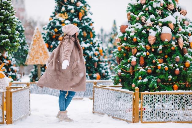 Beautidul donna vicino all'albero di natale nella neve all'aperto