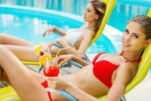 Bellezze a bordo piscina. vista laterale di due belle giovani donne in bikini che bevono cocktail mentre si rilassano sulla sedia a sdraio vicino alla piscina