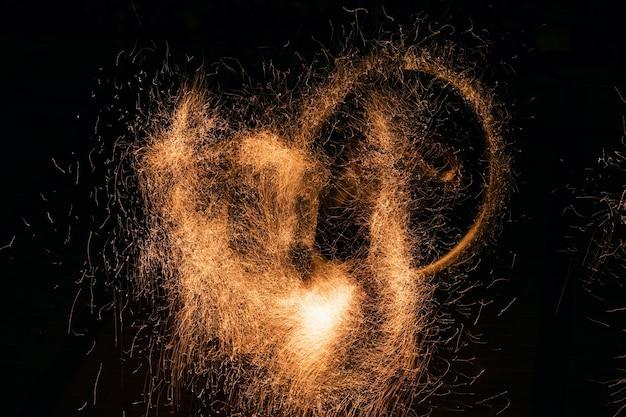 Bellissimo sfondo astratto sul tema della luce del fuoco e della vita che brucia le braci incandescenti che volano via...
