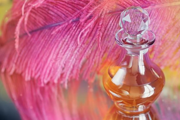 Bellissimo sfondo sfocato astratto morbido con piuma viola e bottiglia di olio profumato o aromatico