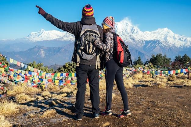 Una donna bella e attiva e un uomo si abbracciano sullo sfondo delle montagne. il concetto di ricreazione attiva e turismo in montagna. coppia innamorata trekking in nepal himalaya.