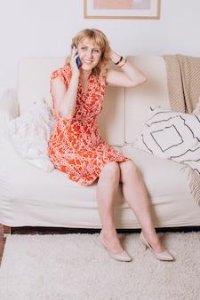 La bella donna bionda adulta è seduta sul divano e parla al telefono
