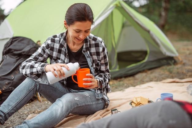 Bella ragazza adulta che beve tè in campeggio nella foresta con tenda sullo sfondo e giovane donna sorridente...