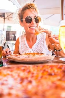 Bella donna di mezza età adulta che si gode una gustosa pizza naturale italiana al ristorante pizzeria - la gente mangia cibo tradizionale italiano - stile di vita sano vegetariano e vegano