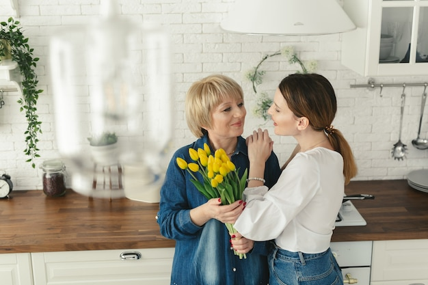 Bella donna adulta che dà i fiori a sua madre matura