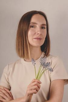 Bella donna adulta che tiene i fiori muscari nelle sue mani