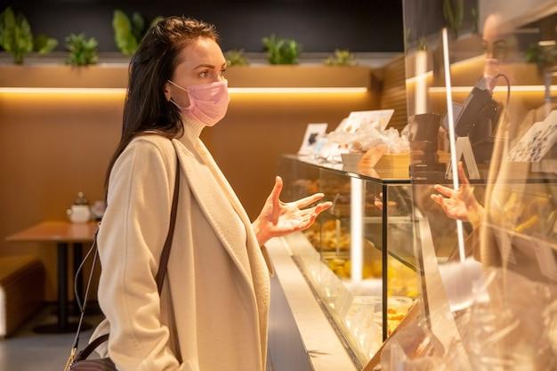 Bella donna adulta in maschera medica ordina cibo e bevande al bar
