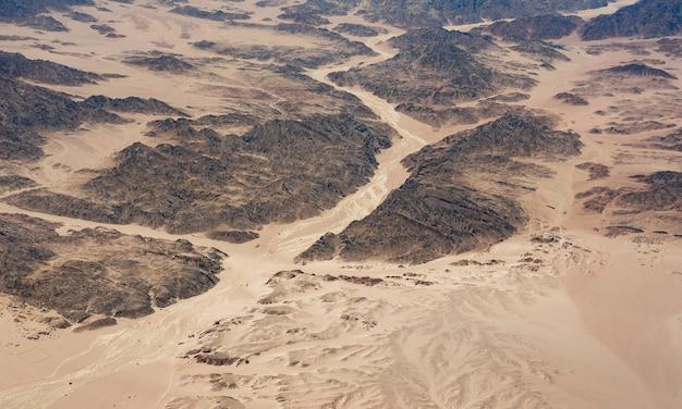 Bello paesaggio di vista aerea delle cime delle montagne nel deserto. deserto del sahara, vista dall'aereo