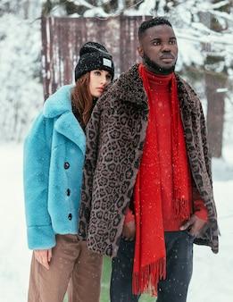 La bella coppia afro-americana e una ragazza di aspetto europeo in una foresta invernale sullo sfondo dell'estate in abiti eleganti. il concetto di estate in inverno.