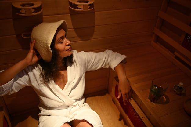 Bella donna di etnia afroamericana che riposa nella sauna a infrarossi. avvicinamento. trattamento termale, terapia di bellezza alternativa.