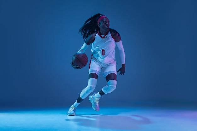 Bello giocatore di pallacanestro femminile afroamericano in movimento e azione in luce al neon sul concetto di parete blu di hobby sport professionale stile di vita sano