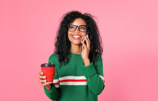La bella ragazza afroamericana in una felpa verde e occhiali neri sta posando con una tazza di caffè rossa nella mano destra e uno smartphone vicino all'orecchio sinistro