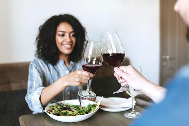 Bella ragazza afroamericana a cena con un amico nel ristorante
