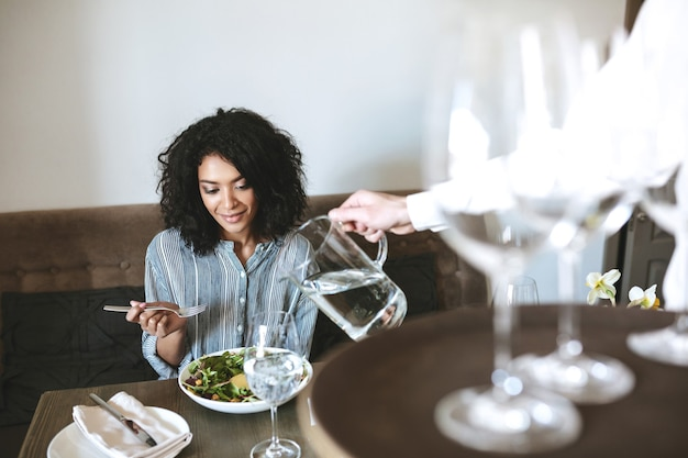 Bella ragazza afroamericana che si siede nel ristorante e che mangia insalata mentre cameriere versando acqua in vetro