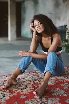 Bella ragazza afroamericana con capelli ricci scuri in top sportivo nero e jeans pensieroso mentre era seduto sul tappeto vintage a casa