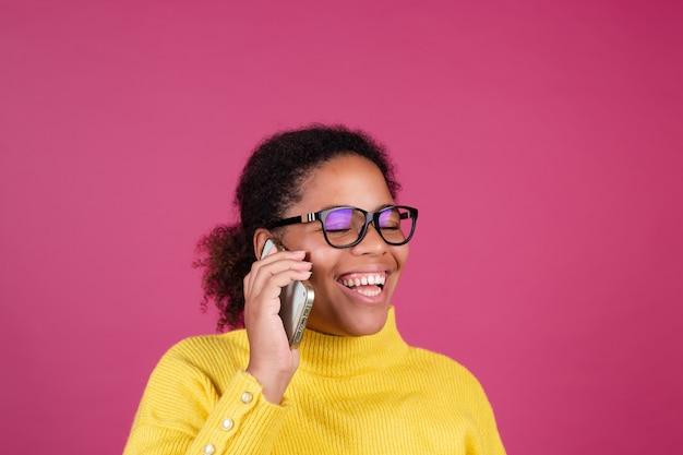 Bella donna afroamericana sulla parete rosa che ha conversazione sul cellulare