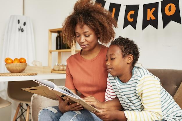 Bella donna afroamericana che si siede sul divano nel soggiorno con il suo figlio preteen che legge il libro di storie di halloween interessante