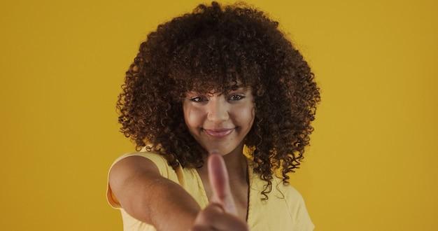 La bella donna afroamericana sta felice e positiva con i pollici in su che approva con un grande sorriso che esprime il gesto giusto.