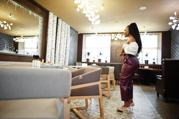 Bella donna afroamericana in camicetta bianca e pantaloni di pelle rossa posa al ristorante.